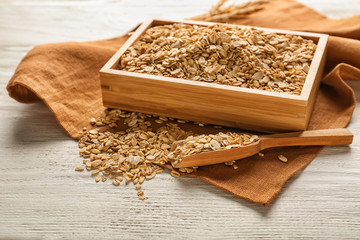 Container with raw oatmeal on wooden table