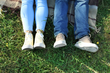 Legs of happy couple lying on grass in park