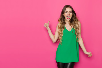Happy Young Woman In Green Top Is Showing Thumb Up And Shouting