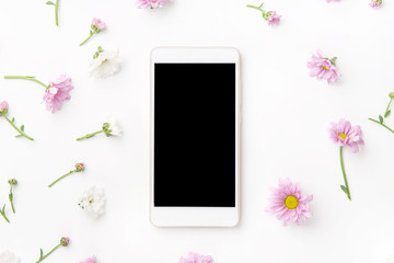 Flatlay with smartphone mock up and floral pattern at white background. Top view