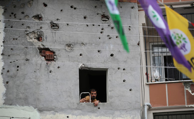 A man watches a campaign event of Turkey's main pro-Kurdish Peoples' Democratic Party from a window of a building which was damaged during the security operations and clashes between Turkish security forces and Kurdish militants, in Silvan