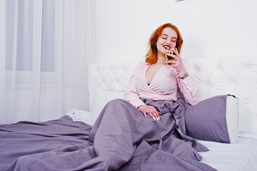 Gorgeous red haired girl in pink blouse and red skirt with glass of wine at hand on the bed at room.