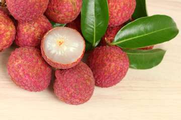 Fresh red lychee and peeled with leaves on wooden background with copy space.