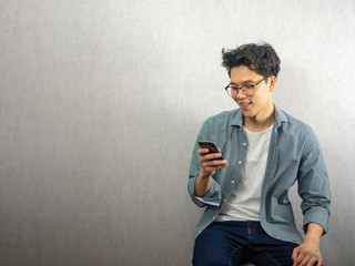 Asian man using phone, happy and smile looking at the screen