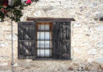 Old window in an ancient white brick wall