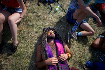 Paul Andreson, 22, lies on the ground as Kamasi Washington performs on the fourth and final day of the Firefly Music Festival in Dover, Delaware U.S.
