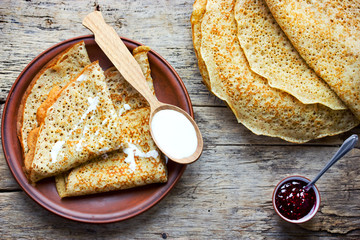 Rye flour pancakes with sour cream and jam on a wooden background top view, rustic style