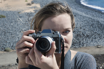Young millennial female of Caucasian ethnicity holding a digital, professional camera over her right eye and taking a photograph facing forward, against a pebble beach background in a sunny day