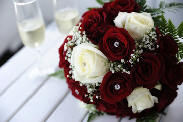 Beautiful red and white roses wedding bouquet on a table with two champagne flutes
