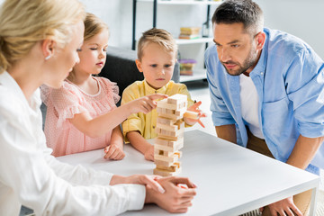 family with two children playing with wooden blocks at home