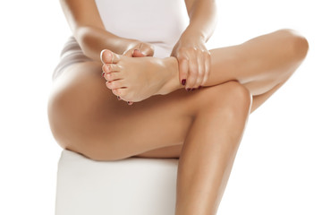women applied body cream on her beautiful legs on white background