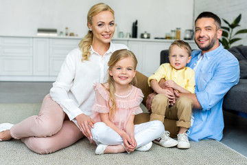 happy family with two kids smiling at camera while sitting together at home