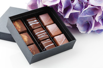 Set of luxury bonbons in box on white background with purple hydrangea flowers