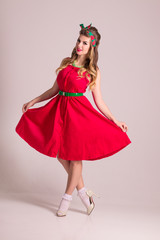 Pretty woman in red dress with hairdo stands in grey studio, pin up style