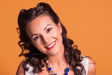 Beautiful brunette with hairdo and make up smiles in studio, pin up style, close up portrait