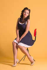 Smiling girl in dress with hairdo sits on chair in yellow studio, pin up style, full body