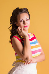 Young woman in striped shirt, with hairdo stands in yellow studio, pin up style