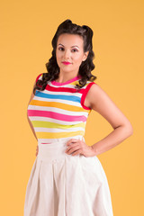 Smiling young woman in striped shirt, with hairdo stands in yellow studio, pin up style