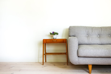 Modern retro interior. A gray couch and vintage table with a potted plant. Empty white wall in background. Copy space for text.