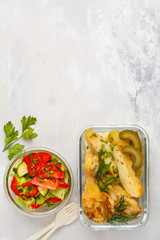 Healthy meal prep containers with baked chicken, potatoes and vegetable salad, top view, copy space
