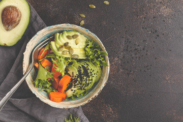 Vegan salad, rainbow bowl with baked sweet potato and avocado, top view, copy space. Healthy vegan food concept.