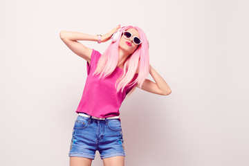 Wall Mural - Girl Listening Music in Headphones Having Fun. DJ Music vibrations. Young Model Woman with Kiss Face Expression, Pink Fashion Hairstyle in Stylish Trendy Summer Outfit.