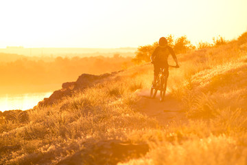 Cyclist Riding the Mountain Bike on the Summer Rocky Trail at the Evening. Extreme Sport and Enduro Cycling Concept.