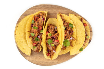 Overhead photo of Mexican tacos with pulled pork, avocado, chili peppers, cilantro, with place for text, on white