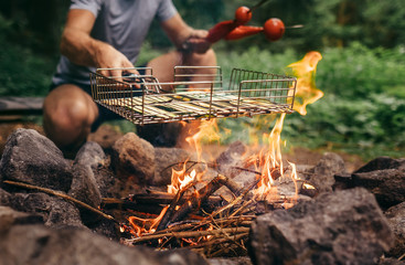 Summertime leisure concept image: man cooks a vegetabels on campfire