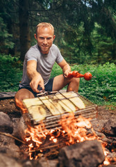 Man holds above campfire grilling grid with sliced vegetables. Summer picnic in forest