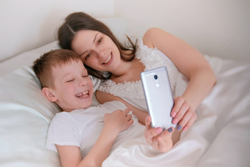 Mom and son take selfie on her mobile phone. Morning in bed.