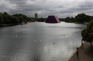 Swans paddle in front of Christo's work The London Mastaba, on the Serpentine in Hyde Park, London