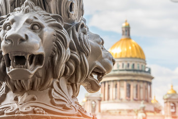 Saint Isaac's Cathedral out of focus, in the foreground the sculpture of lions on a pillar. Saint-Petersburg, Russia.