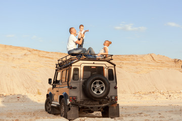Portrait of a young family with son on the roof of the car in the desert.