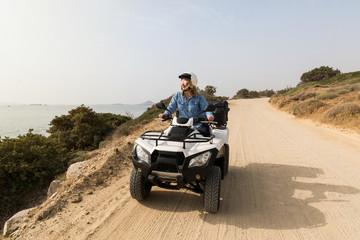 Young woman driving rental quad bike on seaside road in Naxos island, Greece