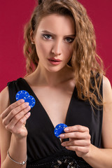 Beautiful woman with casino chips on red background. Portrait