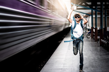 Traveler man running after a moving train
