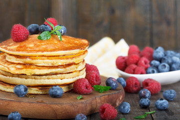 American sweet breakfast. Stack of homemade pancakes with fresh blueberries, raspberries and maple syrup. Rustic background with wooden board.