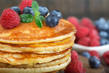 Closeup of homemade american pancakes, with fresh blueberries, raspberries and maple syrup on a rustic wooden  background