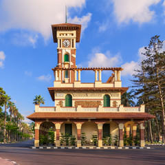 Facade of the clock tower in Montaza public park with decorated stone wall, green wooden window shutters, and red tile canopies after sunrise, Alexandria, Egypt