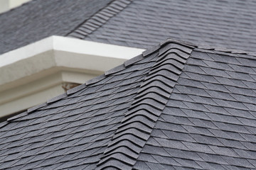 edge of Roof shingles on top of the house, dark asphalt tiles on the roof background.