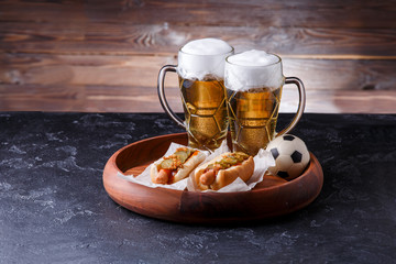 Picture of two glasses of beer, hot dogs, soccer ball