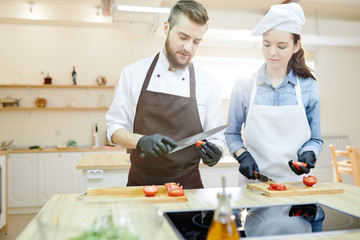 Waist up portrait of professional cook working in restaurant kitchen with su-chef, both cutting vegetables standing at wooden workstation, copy space