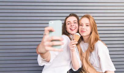Portrait of two stylish women in the light summer clothes that take selfie on phone. Two pretty girlfriends take a selfie on the background of a gray wall.