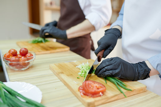 Closeup of unrecognizable female chef cutting vegetables standing at wooden table in restaurant kitchen, copy space