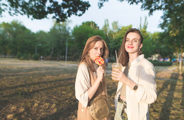 Two attractive girls are in the park, holding lemonade and lollipops in their hands and looking at the camera. Cute stylish girlfriends walking around the park.