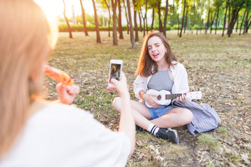 Girl takes a camera on the smartphone as a girlfriend plays ukulele in the park. The girl takes the cover of the song on the camera. Leisure with a girlfriend and musical artist in the park.