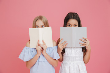 Picture of excited or frightened european girls 8-10 wearing dresses covering their faces with books, isolated over pink background Wall mural