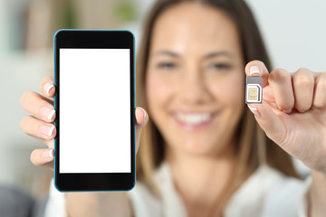 Woman hand showing a sim card and a smart phone