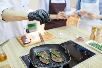 Closeup of unrecognizable professional chef cooking meat on frying pan while cooking in modern restaurant kitchen, copy space